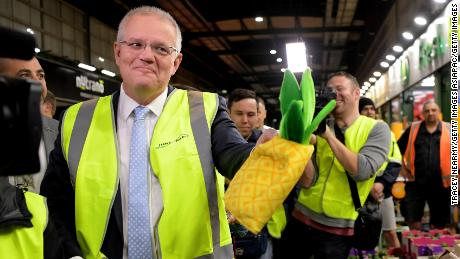 Prime Minister Scott Morrison is given a pineapple hat from a vendor as he visits the Sydney Markets on May 16.