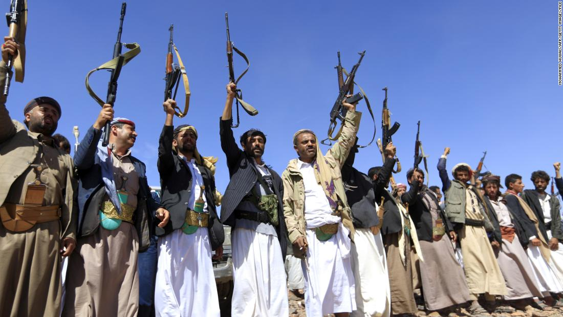 Armed men raise their weapons as they gather near Sanaa to show their support of the Houthi movement in February.