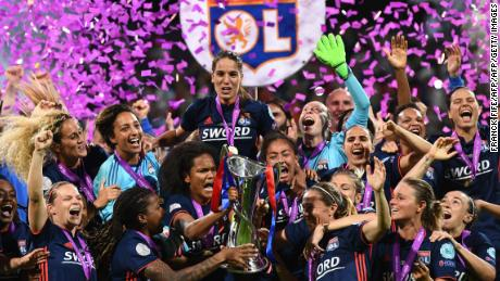 TOPSHOT - Olympique Lyonnais' French defender Wendie Renard (C) holds the trophy with teammates as they celebrate their victory after the UEFA Women's Champions League final football match Vfl Wolfsburg vs Olympique Lyonnais at the Valeriy Lobanovsky stadium in Kiev on May 24, 2018. - Olympique Lyonnais won 4-1, their third trophy in a row. (Photo by FRANCK FIFE / AFP)        (Photo credit should read FRANCK FIFE/AFP/Getty Images)