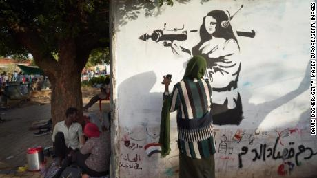 A woman paints an image of a female fighter near a protest site in Khartoum on May 2.