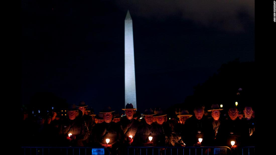 "Law enforcement personnel attend a candlelight vigil on the National Mall in Washington on Monday, May 13. The annual vigil commemorates new names that have been added to the National Law Enforcement Officers Memorial. Nineteen weeks into 2019, 18 officers across the country <a href=""https://www.cnn.com/2019/02/07/us/2019-officers-killed-trnd/index.html"" target=""_blank"">had been shot and killed in the line of duty.</a>"