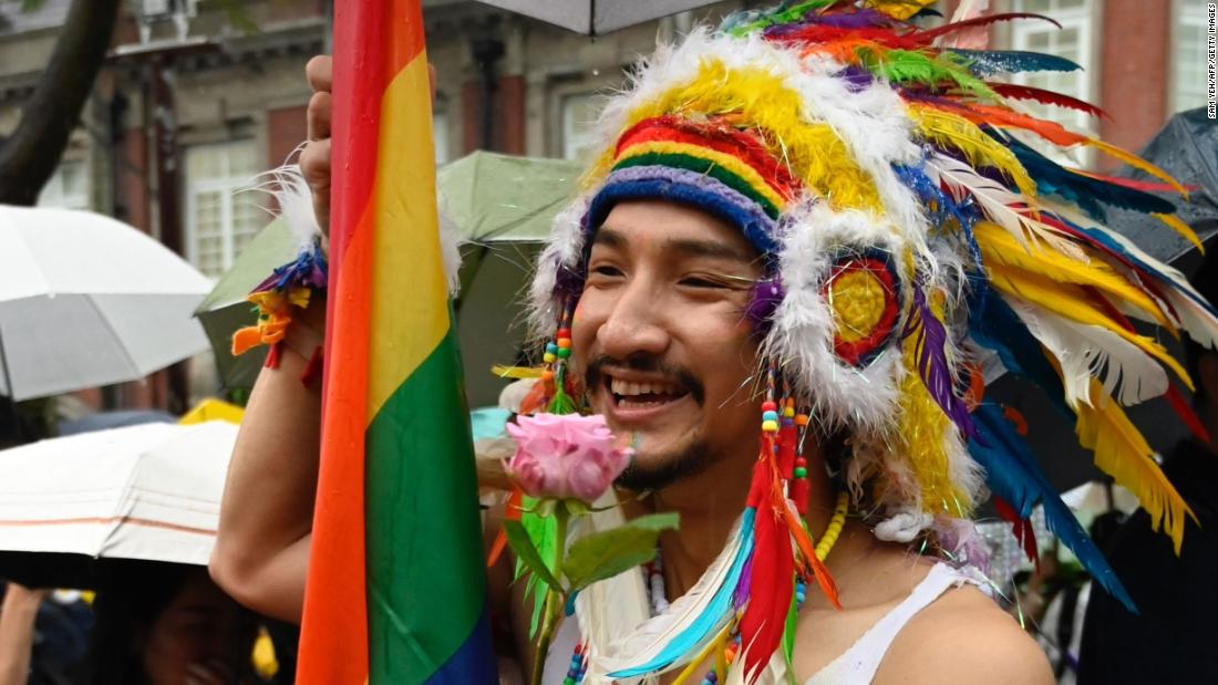 A gay rights advocate holds a flower in  support of the same-sex marriage law.