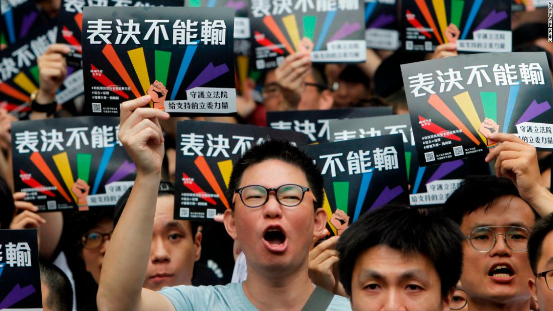 Same-sex marriage supporters gather outside the Legislative Yuan in Taipei, Taiwan. The signs read, ''Vote Can't Be Defeated.''