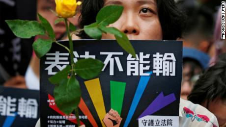 A same-sex marriage supporter holds rose to mourn those who committed suicide due to discrimination during a parliament vote on three draft bills of a same-sex marriage law, outside the Legislative Yuan in Taipei.