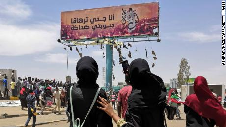 "TOPSHOT - A woman takes a photograph with her smarphone of a billboard showing a reproduction of a picture of Alaa Salah, a Sudanese woman who has become an icon of the protest movement after a video of her leading demonstrators' chants went viral, in the capital Khartoum on April 14, 2019. - Sudan's foreign ministry on today urged the international community to back the country's new military rulers to help ""democratic transition"". (Photo by ASHRAF SHAZLY / AFP)        (Photo credit should read ASHRAF SHAZLY/AFP/Getty Images)"
