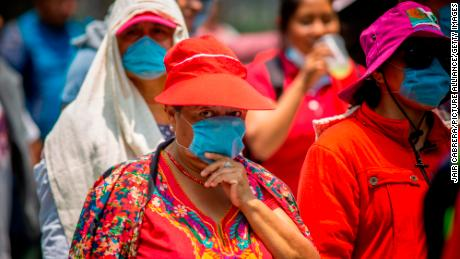 Pedestrians cover their mouths and noses in Mexico City