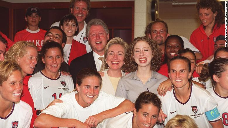 US President Bill Clinton (L), First Lady Hillary Clinton (C) and daughter Chelsea Clinton with members of the U.S. Women's soccer team in the locker room.