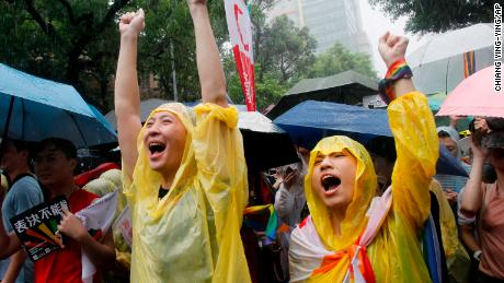 Same-sex marriage supporters cheer outside the Legislative Yuan in Taipei, Taiwan, Friday, May 17, 2019 after Taiwan's legislature has passed a law allowing same-sex marriage in a first for Asia. The vote Friday allows same-sex couples full legal marriage rights, including in areas such as taxes, insurance and child custody. (AP Photo/Chiang Ying-ying)