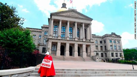 "TOPSHOT - Activist Tamara Stevens with the Handmaids Coalition of Georgia leaves the Georgia Capitol after Democratic presidential candidate Sen. Kirsten Gillibrand (D-NY) addressed an event to speak out against the recently passed ""heartbeat"" bill on May 16, 2019 in Atlanta, Georgia. - The bill, which bans abortions after a fetal heartbeat is detected around six weeks, was signed on May 15 by Alabama Governor Kay Ivey. Under the new measure, expected to come into effect in six months, performing an abortion is a crime that could land doctors in prison for up to 99 years. (Photo by John Amis / AFP)        (Photo credit should read JOHN AMIS/AFP/Getty Images)"