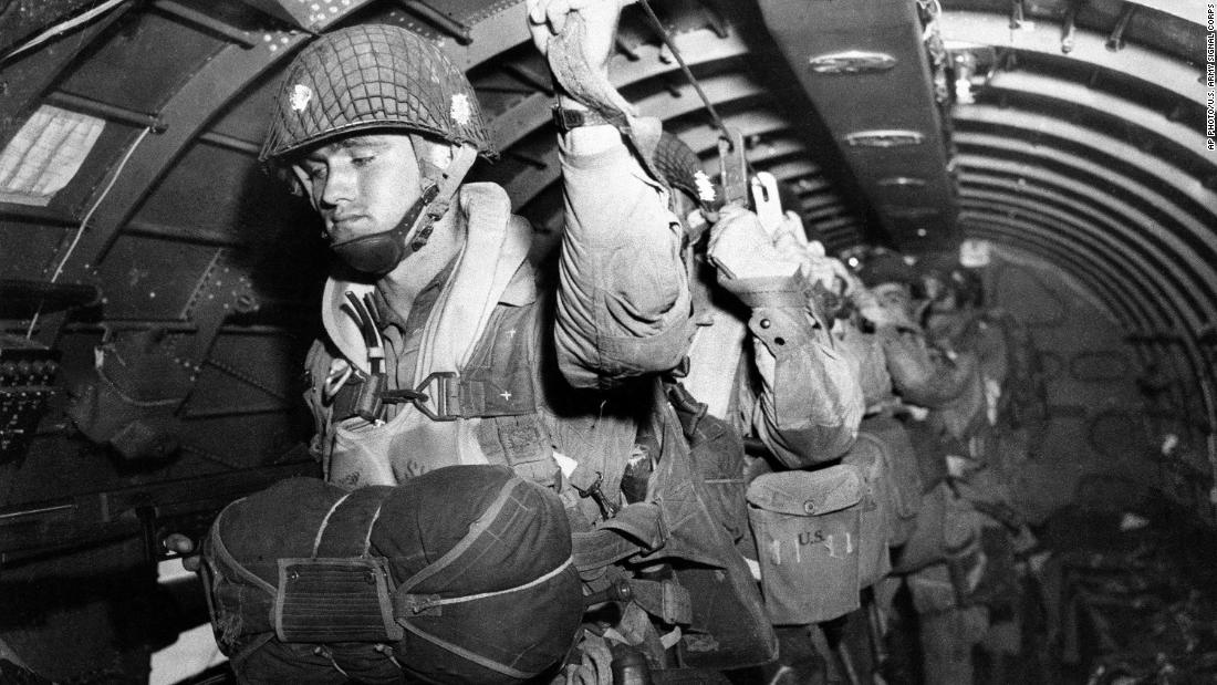 US paratroopers fix their static lines before a jump over Normandy on D-Day.