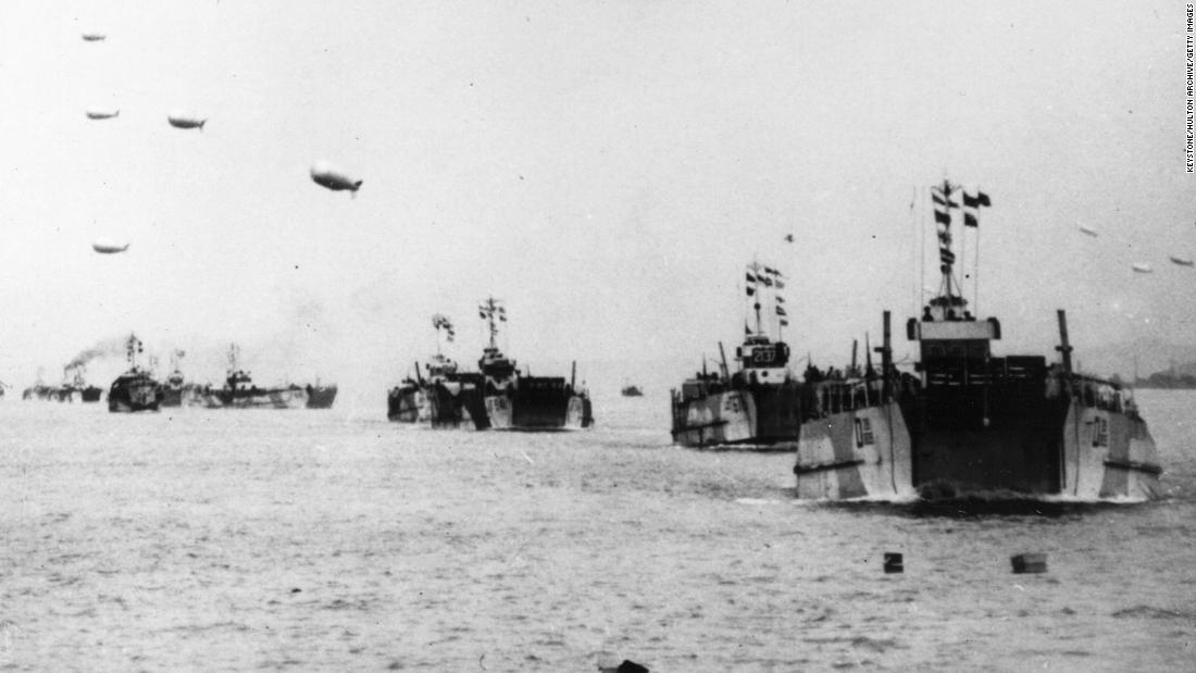 Tank landing ships, each towing a protective barrage balloon, leave the English coast carrying supplies to the French beachhead.