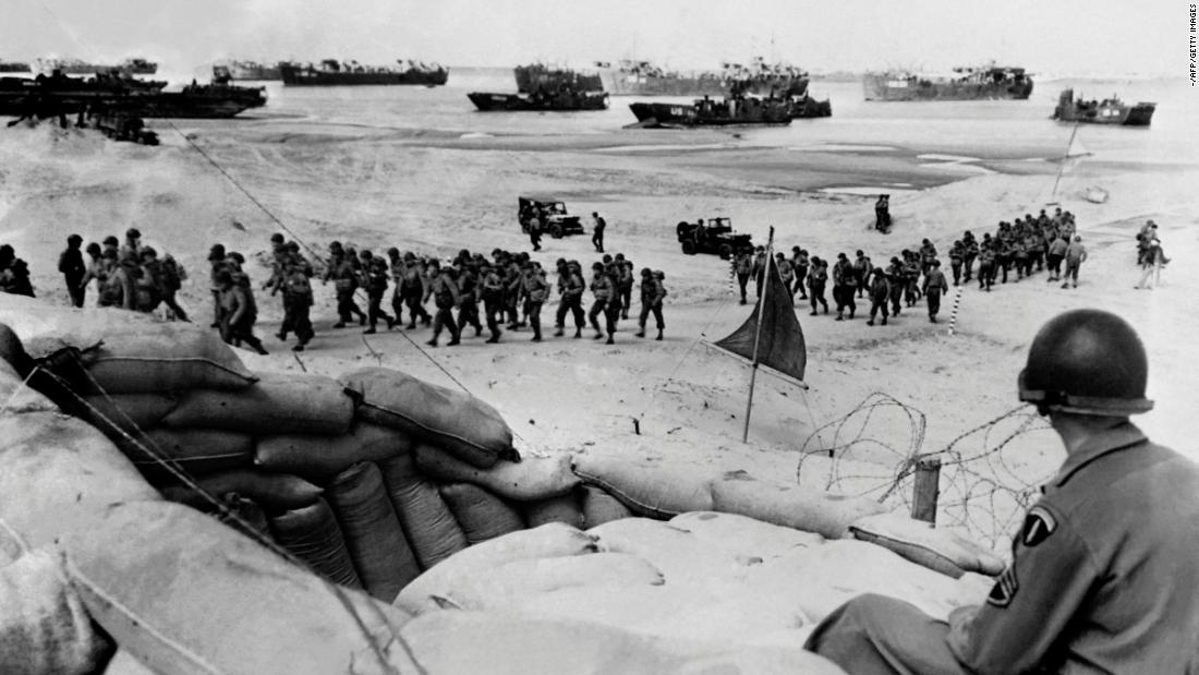 Allied soldiers arrive on a beach.