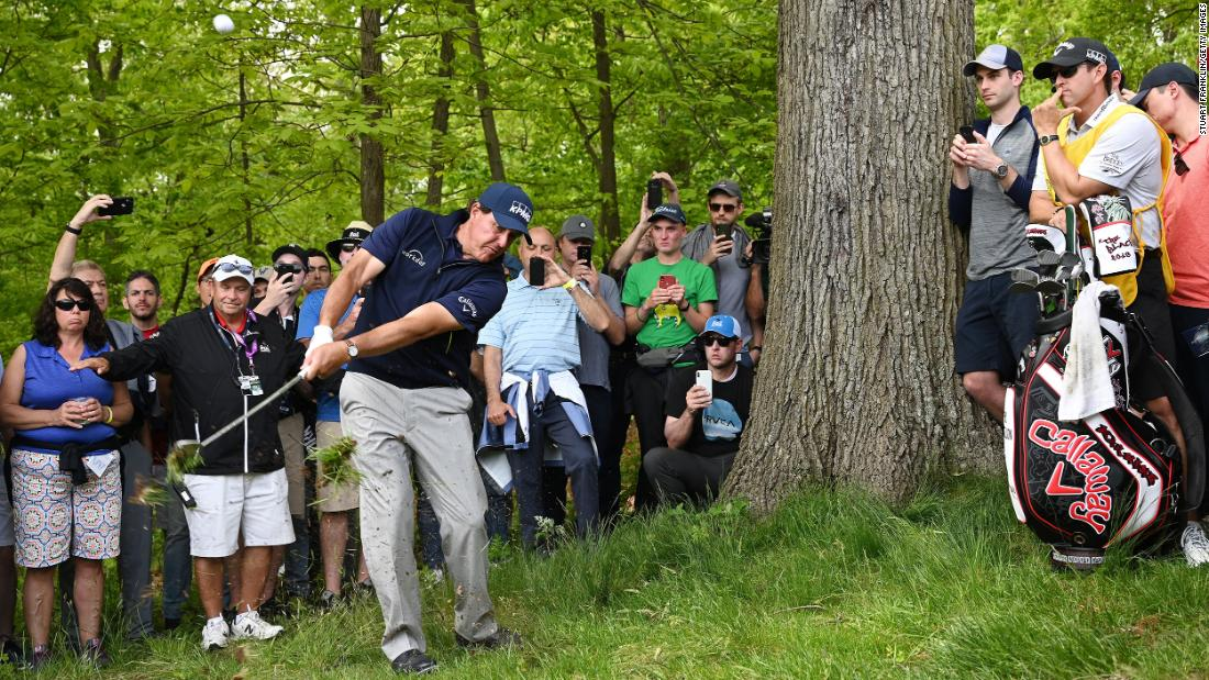 Phil Mickelson plays a shot from the rough on the third hole.