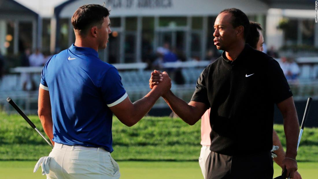 Brooks Koepka, left, shakes hands with Tiger Woods after finishing the second round.