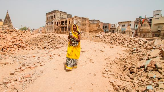 A woman walks through a demolition site, where buildings have been cleared to make way for the Kashi Vishwanath temple corridor in Varanasi.