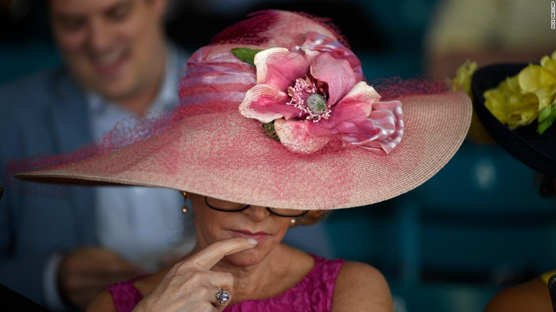 A spectator looks over a form ahead of the 144th Preakness Stakes horse race at Pimlico Race Course Saturday.