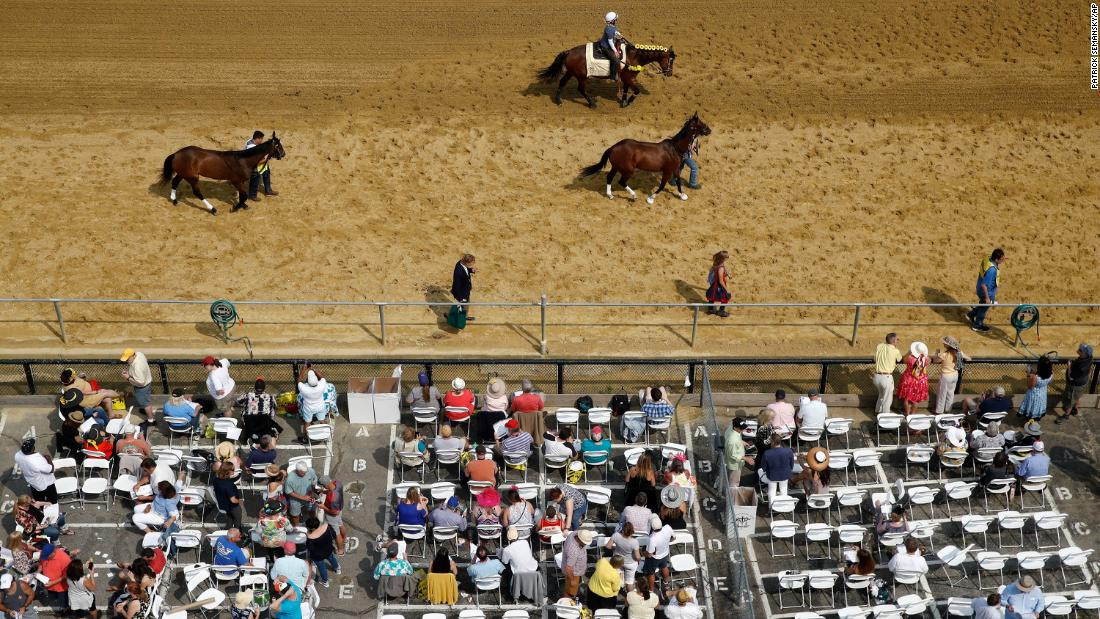 Spectators gather as horses pass on the track at Pimlico Race Course ahead of the Preakness Stakes horse race Saturday.