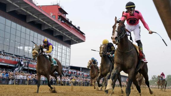 Jockey Tyler Gaffalione, right, riding War of Will, reacts as they cross the finish line first to win the Preakness Stakes horse race at Pimlico Race Course on Saturday, May 18, in Baltimore.