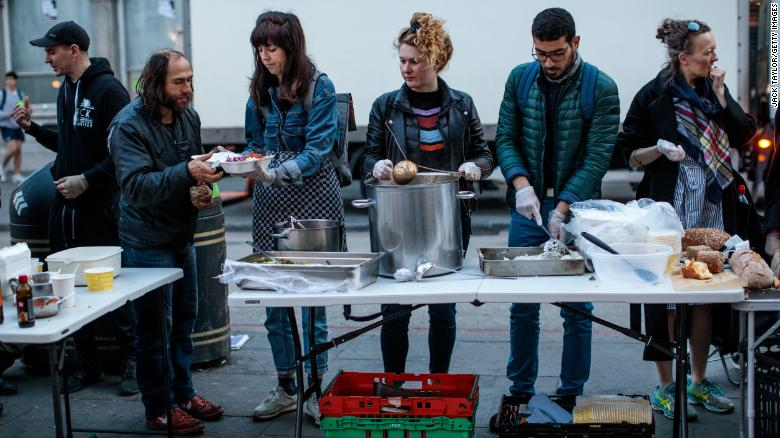 A free hot meal is served by volunteers from Refugee Community Kitchen to people outside Camden Town Underground Station on April 17 in London, England.