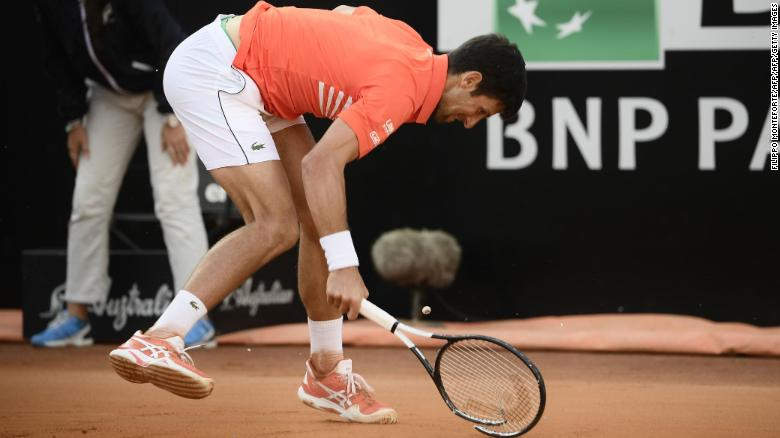 Novak Djokovic smashes his racquet after being broken.