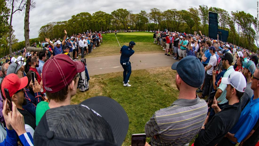 Tyrrell Hatton of England makes a shot out of the rough amidst the gallery on the ninth hole during the final round.