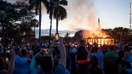 Crowds watch as a temporary art installation burns Sunday in Coral Springs, Florida.