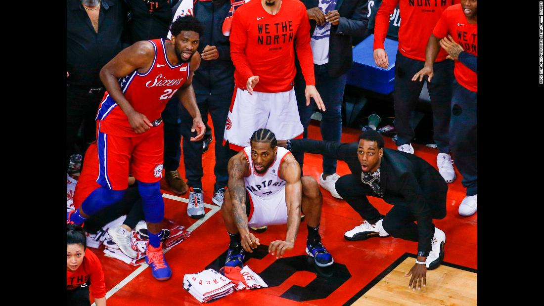 Philadelphia 76ers center Joel Embiid, left, and Toronto Raptors guard Jordan Loyd, right, look on as Kawhi Leonard, center, waits for his last-second shot to drop through the hoop during Game 7 of the NBA Eastern Conference Semi-finals on Sunday, May 12 in Toronto. The shot bounced on the rim four times before finally falling through the bottom of the net to clinch the victory for Toronto.