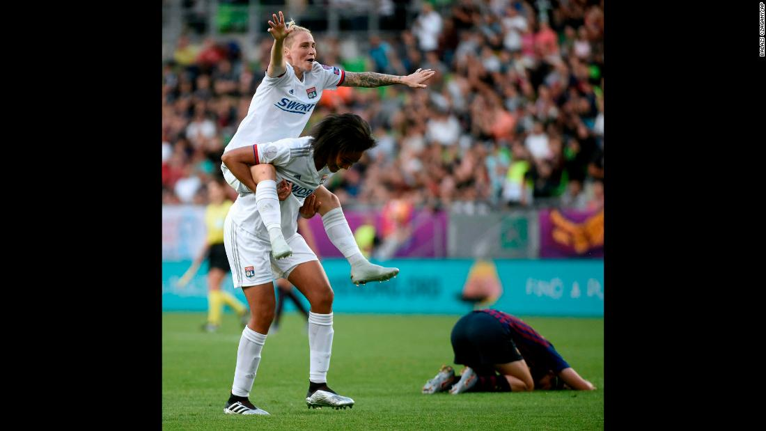 Jessica Fishlock of Olympique Lyonnais rides on the back of teammate Wendie Renard after defeating Barcelona 4-1 in the Women's Champions League final match in Budapest, Hungary on Saturday, May 18.