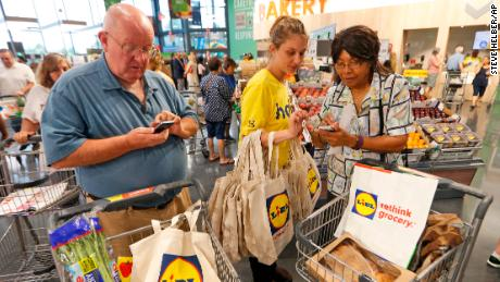 Lidl employee Jessica Donna, center, helps shoppers with the Lidl app during the grand opening of one of the first Lidl grocery stores in the United States, Thursday, June 15, 2017, in Virginia Beach, Va. Several Lidl stores opened across the nation on Thursday. (AP Photo/Steve Helber)