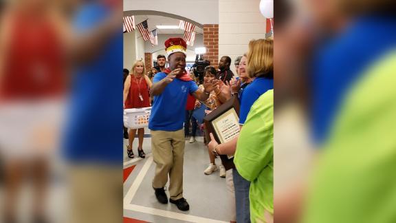 "John Lockett greets faculty members at Sand Hill Elementary on ""Mr. John Day."""