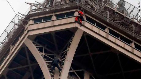 A rescue worker hangs from the Eiffel Tower Monday, May 20, 2019 in Paris. The Eiffel Tower has been closed to visitors after a person has tried to scale it. (AP Photo/Michel Euler)