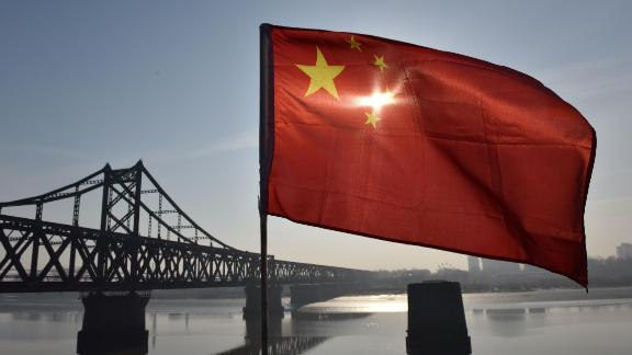 TOPSHOT - The Chinese flag flies on the Yalu River Broken Bridge, with the Sino-Korean Friendship Bridge, and the North Korean city of Sinuiju behind, in the border city of Dandong, in China