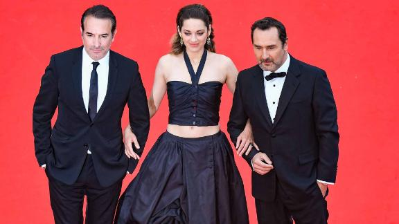 Marion Cotillard (flanked by French actors Jean Dujardin and Gilles Lellouche) wears a halterneck crop top and matching floor-length skirt.