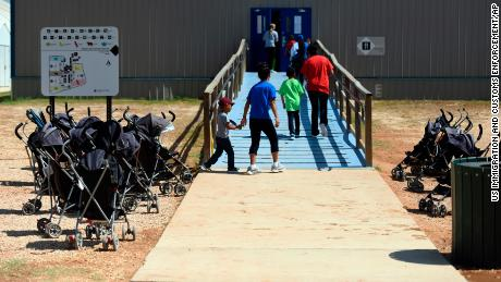 In this August 2018 photo provided by US Immigration and Customs Enforcement, immigrants enter a building at the South Texas Family Residential Center in Dilley, Texas.