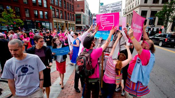 Planned Parenthood patients and supporters surround a man during a rally in Monument Square.