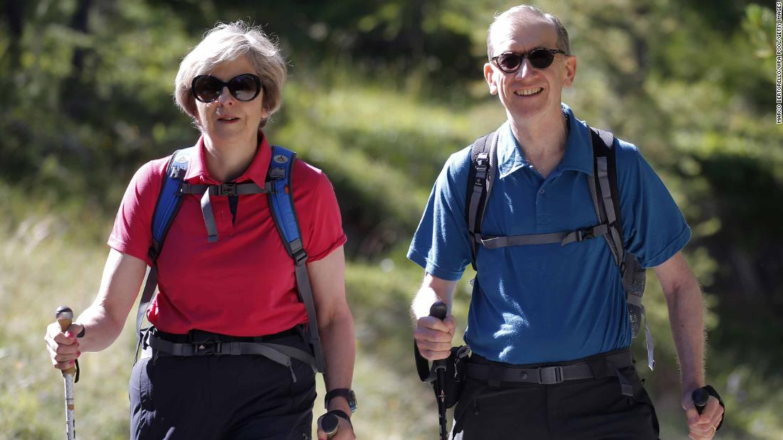 May walks with her husband, Philip, while they vacationed in the Swiss Alps in August 2016.