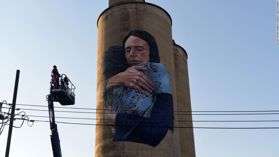A painter has revealed an 80-foot mural of New Zealand's prime minister comforting woman after mosque attacks
