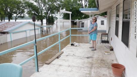 Marlene Paul stands on the back porch of her Webbers Falls home and watches water from the Arkansas River approach May 22, 2019. (Mike Simons/Tulsa World via AP)