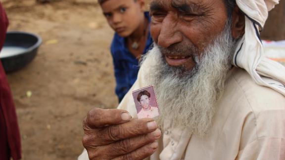 Suleman Khan holds the photograph he has of his son, Rakbar Khan.
