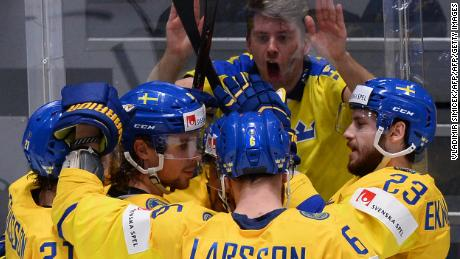 Sweden's players celebrate next to a fan during a 5-4 victory over Latvia.