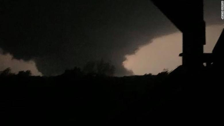 "A ""wedge"" tornado that tore through Missouri's capital is illuminated by a lightning strike near Euguene."