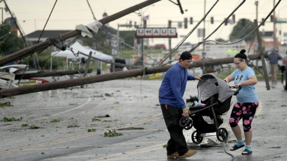 Jessica Rodgers and Ray Arellana carry a stroller over downed power lines  Thursday in Jefferson City.