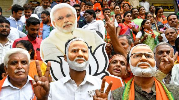TOPSHOT - Indian supporters and party workers of Bharatiya Janata Party (BJP) wear masks of Indian Prime Minister Narendra Modi and flash victory signs as they celebrate on the vote results day for India
