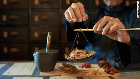 Man measuring ingredients in traditional Asian apothecary