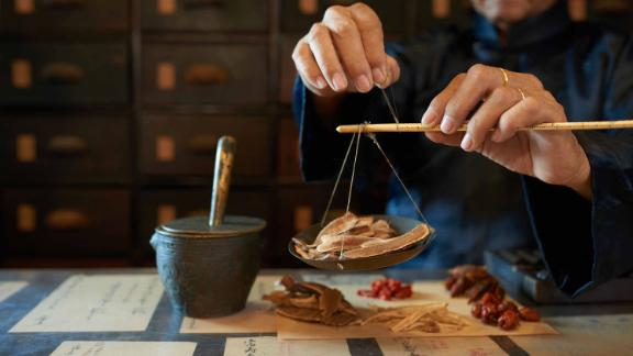 A man measures ingredients in a traditional Asian apothecary.