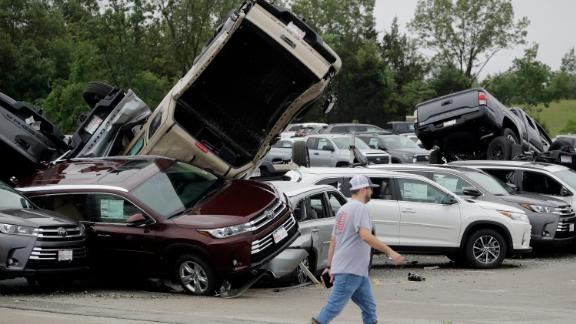 A worker walks past storm-damaged Toyotas on Thursday at a car dealership in Jefferson City.