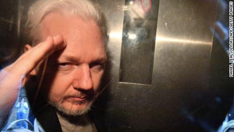 WikiLeaks founder Julian Assange gestures from the window of a prison van as he is driven out of Southwark Crown Court in London on May 1, 2019, after having been sentenced to 50 weeks in prison for breaching his bail conditions in 2012. - A British judge on Wednesday sentenced WikiLeaks founder Julian Assange to 50 weeks in prison for breaching his bail conditions in 2012. Assange took refuge in Ecuador's London embassy to avoid extradition to Sweden and was only arrested last month after Ecuador withdrew his asylum status. (Photo by Daniel LEAL-OLIVAS / AFP)        (Photo credit should read DANIEL LEAL-OLIVAS/AFP/Getty Images)