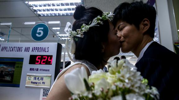 Xue Chen, left, and Antonia Chen, right, kiss after registering their marital status on Friday.