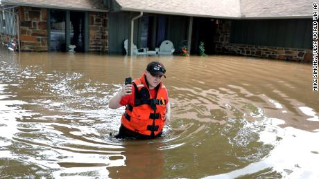 Tulsa County Sheriff's Deputy Miranda Munson makes her way back to a fan boat after checking a flooded house for occupants in the Town and Country neighborhood in Sand Springs, Okla., Thursday, May 23, 2019. Storms and torrential rains have ravaged the Midwest, from Texas through Oklahoma, Kansas, Nebraska, Iowa, Missouri and Illinois, in the past few days. (Mike Simons/Tulsa World via AP)