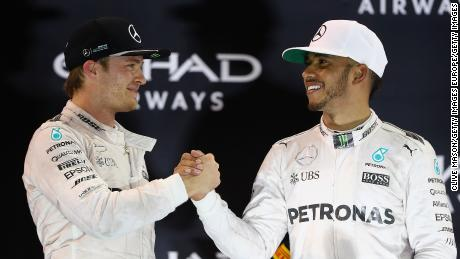 ABU DHABI, UNITED ARAB EMIRATES - NOVEMBER 27:  Race winner Lewis Hamilton of Great Britain and Mercedes GP shakes hands with second place finisher and F1 World Drivers Champion Nico Rosberg of Germany and Mercedes GP on the podium  during the Abu Dhabi Formula One Grand Prix at Yas Marina Circuit on November 27, 2016 in Abu Dhabi, United Arab Emirates.  (Photo by Clive Mason/Getty Images)